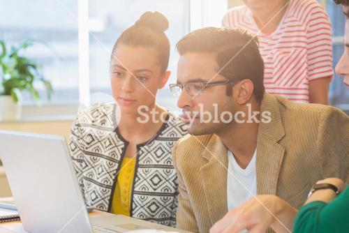 Colleagues using laptop in office