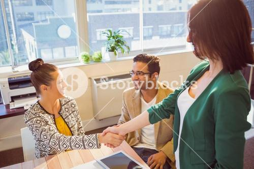 Casual business people shaking hands at desk and smiling