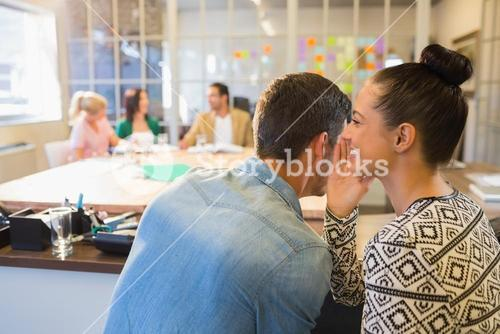 Casual businesswoman whispering secret to her colleague