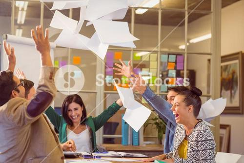 Celebrating business people throwing papers in the air