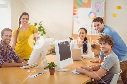 Smiling business team working on laptops
