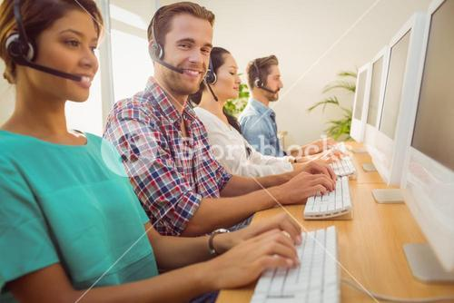 Smiling businessman working in a call centre