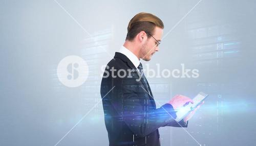 Composite image of businessman in reading glasses using his tablet pc