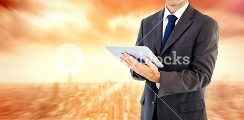 Composite image of serious charismatic businessman holding a tablet computer