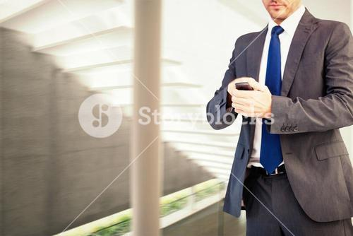 Composite image of focused businessman texting on his mobile phone