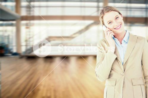 Composite image of businesswoman using her mobile phone