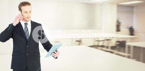 Composite image of serious businessman on the phone holding tablet