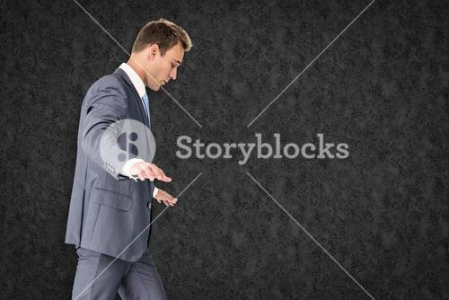 Composite image of businessman walking