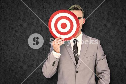 Composite image of businessman holding target