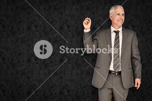 Composite image of businessman holding marker