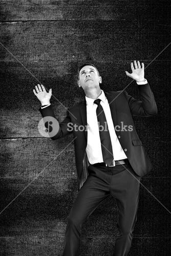 Composite image of businessman with hands up
