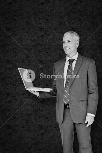 Composite image of businessman using laptop