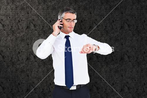 Composite image of businessman on the phone looking at his wrist watch