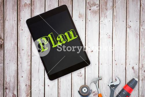 Plan against tools and tablet on wooden background