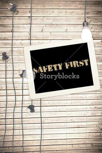 Safety first against tablet and plugs on wooden background