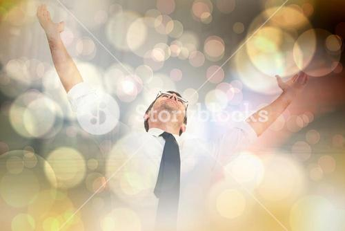 Composite image of handsome businessman cheering with arms up