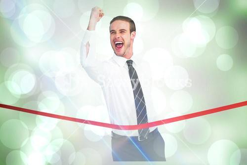 Composite image of businessman crossing the finish line while clenching fist