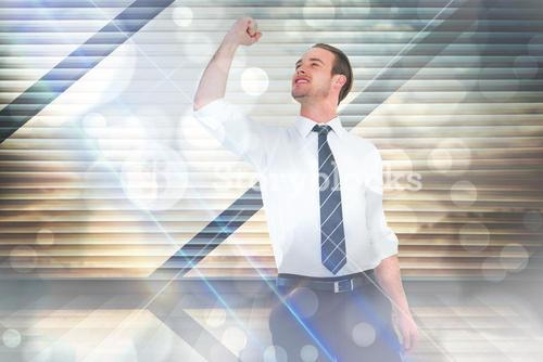 Composite image of businessman cheering with clenched fist