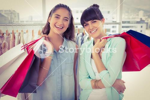 Smiling friends holding shopping bags
