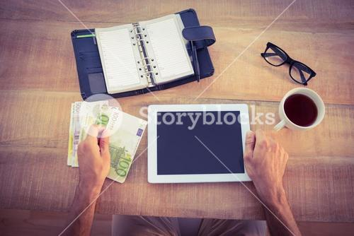 Money bundle and digital tablet on the table
