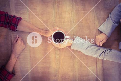 Two hands warming a cup of coffee