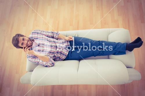 Businessman on the phone extended on the sofa
