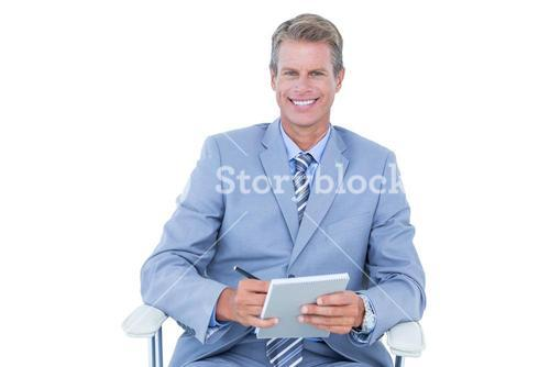 Businessman writing down on a notebook