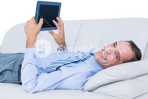 Relaxing businessman on a sofa with a tablet