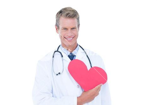 Smiling doctor holding heart card
