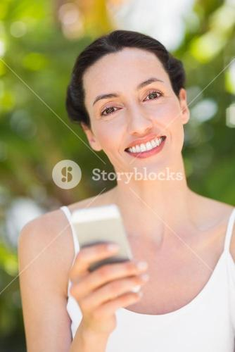 woman in white looking at her phone