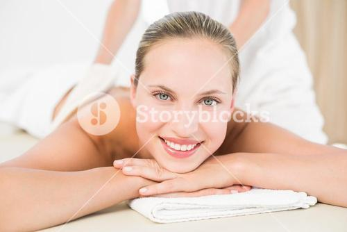 Peaceful blonde enjoying an exfoliating back massage