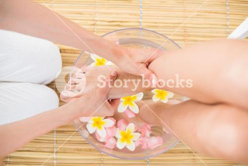 woman washing her feet in a bowl of flower
