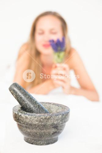 Beautiful blonde lying on massage table with mortar and pestle