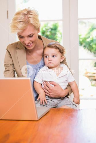 Pretty blonde woman with his son using laptop