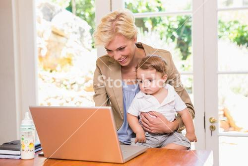 Smiling pretty blonde woman using laptop with his son