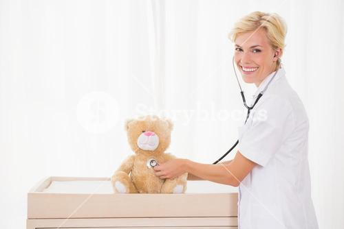 Smiling blonde doctor with stethoscope in the teddy bear