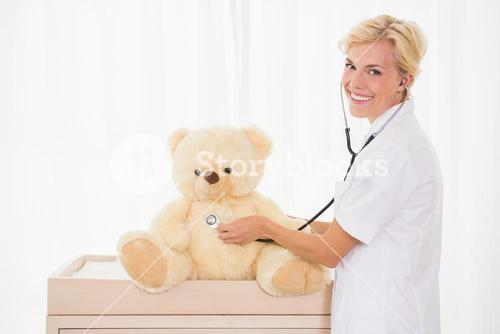 Portrait of a blonde doctor with stethoscope and teddy bear