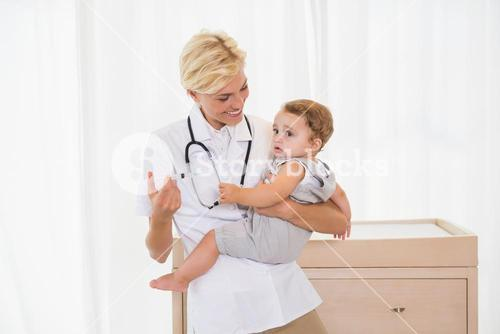 Smiling blonde doctor and child with stethoscope
