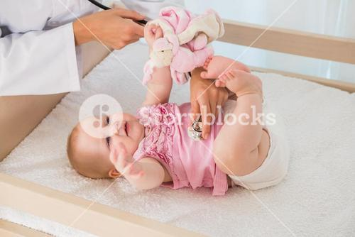 Beautiful cute baby girl with doctor with stethoscope