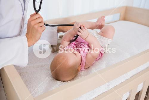 Beautiful cute baby girl with doctor using stethoscope