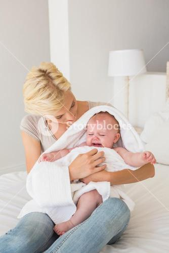 Beautiful mother with her baby girl wrapped up in a towel