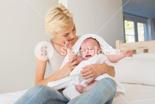 Happy mother with her baby wrapped up in a towel