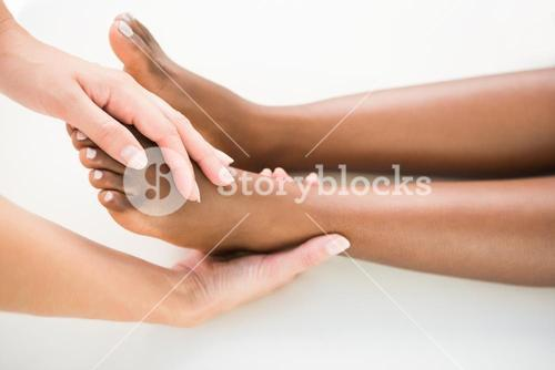 Close-up of a young woman receiving foot massage