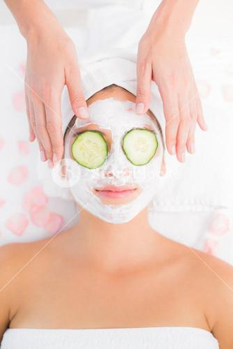Attractive woman receiving cucumber treatment