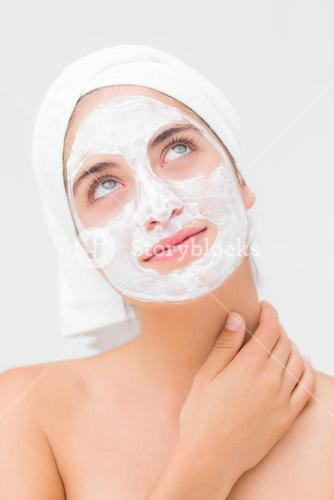 Thoughtful woman having white cream on her face