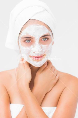 Pretty woman having white cream on her face