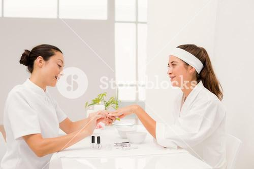 Beautiful woman with beautician applying nail varnish to female clients nails