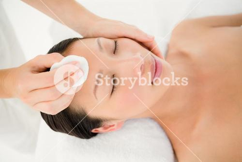 Hands cleaning woman face with cotton swabs