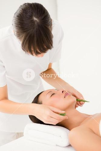 Attractive young woman receiving aloe vera massage