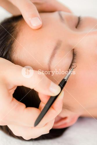Woman placing fake eyelash on a patient